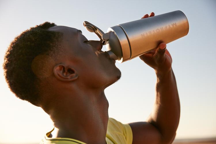 o atleta a beber um suplemento de cafeína