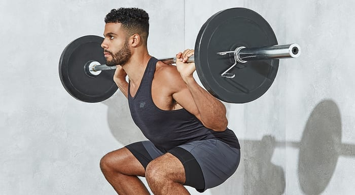 man squatting with barbell