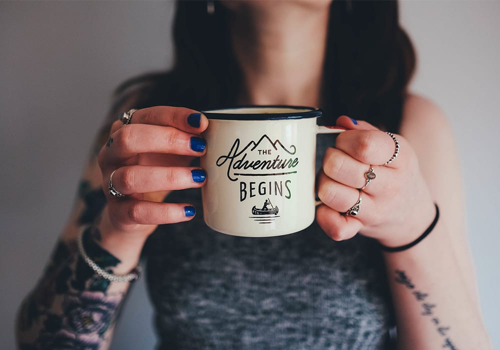 Tattowierte Frau hält Kaffebecher hoch, The Adventure begins, girl with coffeecup tattoo