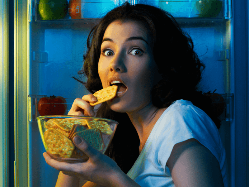 A woman sneaking crackers from the fridge