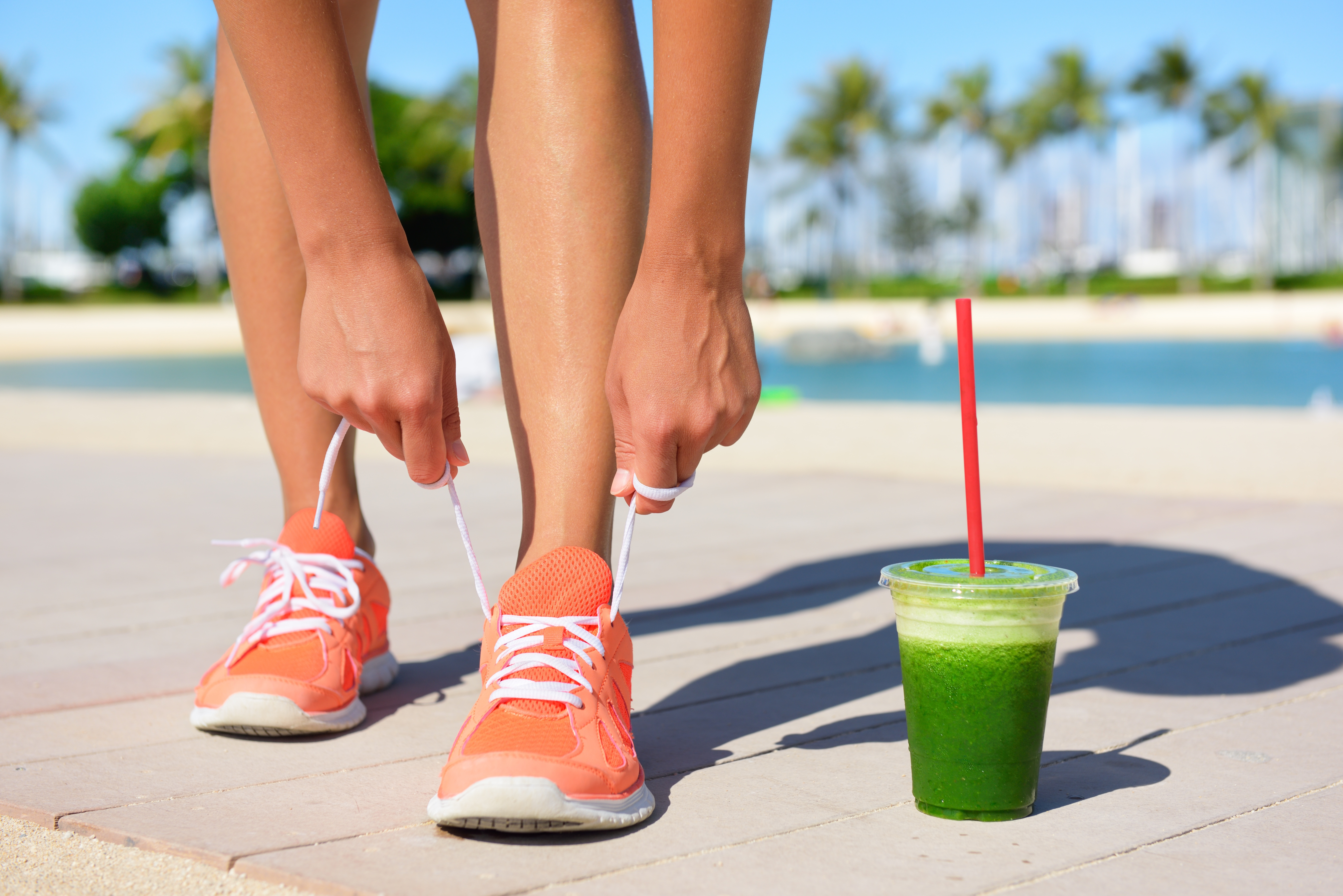 Girl jogging with a green smoothie