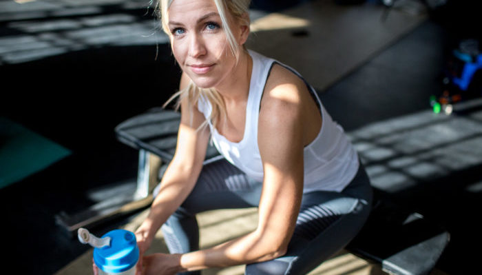 Trainer Kami drinking high protein IdealShake post-workout.