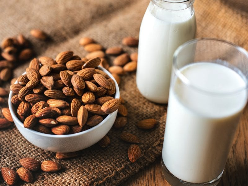 Some almonds and a glass of almond milk