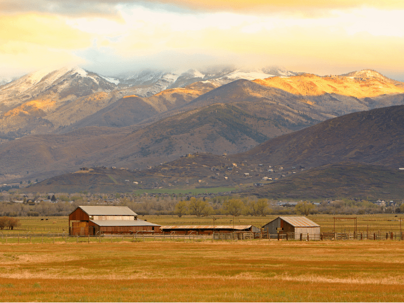 A barn in a pasture near some majestic mountains
