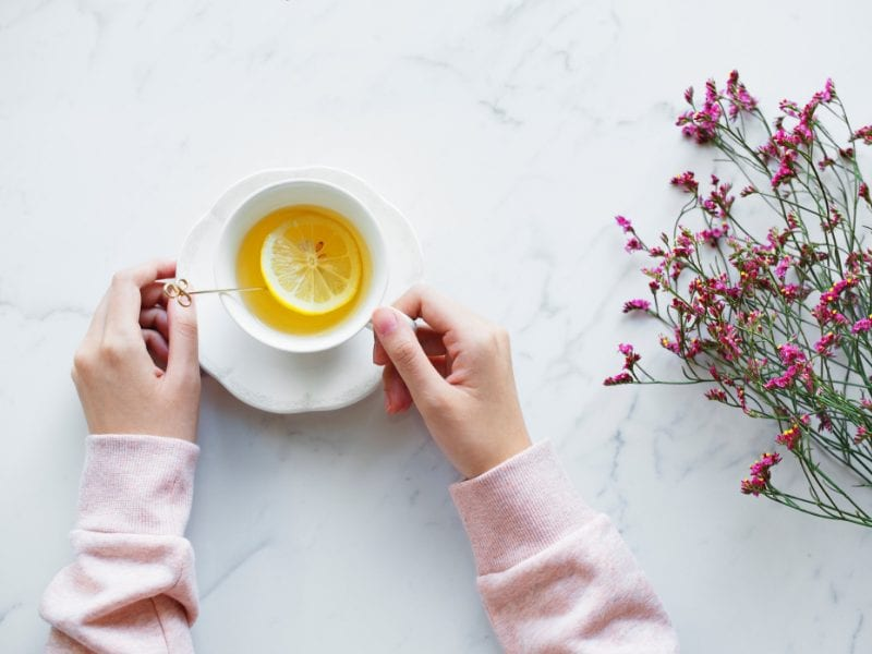 A woman drinking a cup of lemon tea