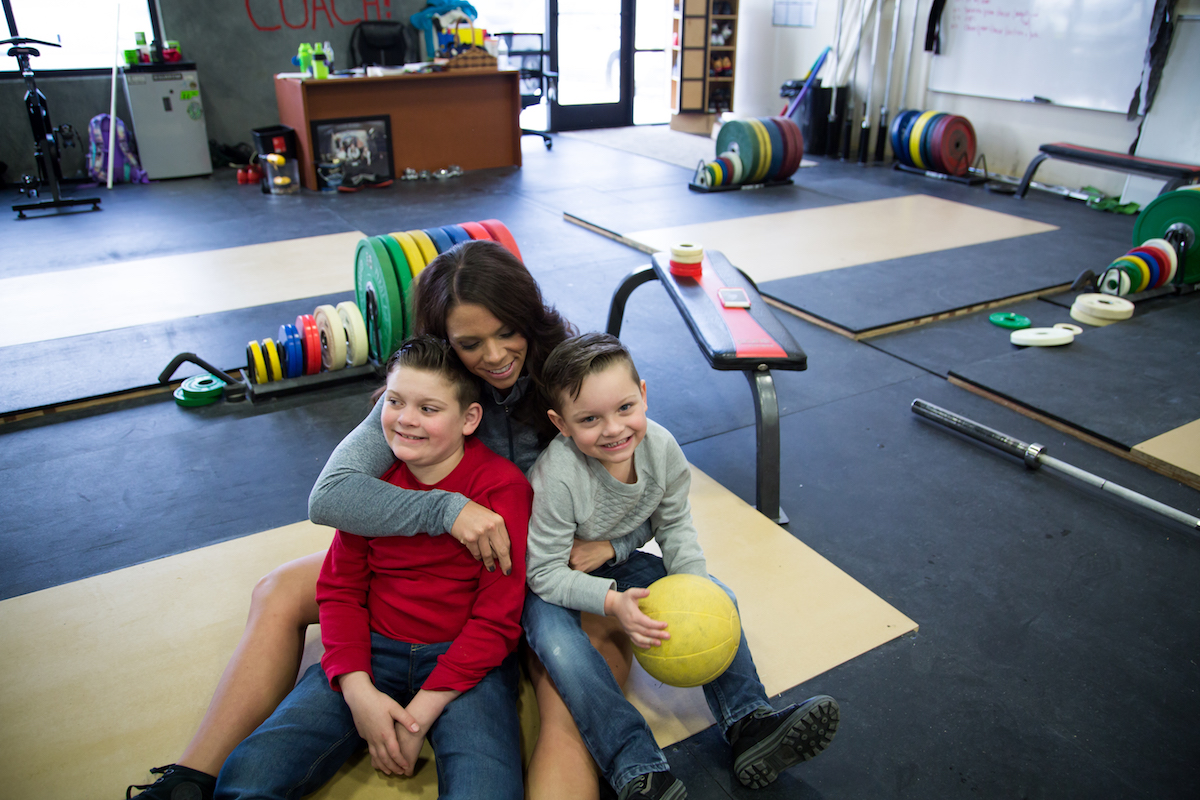 woman at the gym with two young sons