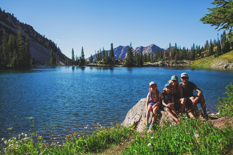 family posing next to lake