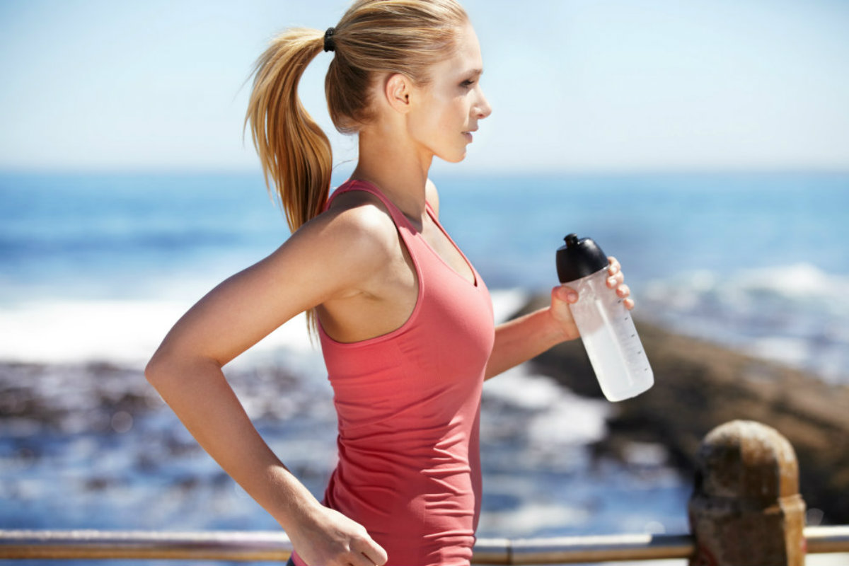 woman running with water bottle in her hands