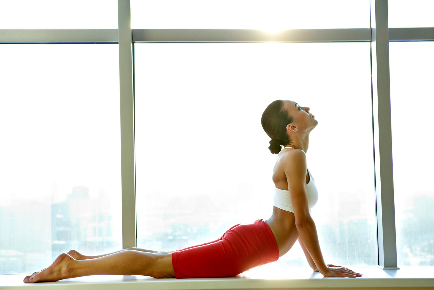 woman doing yoga in front of a window