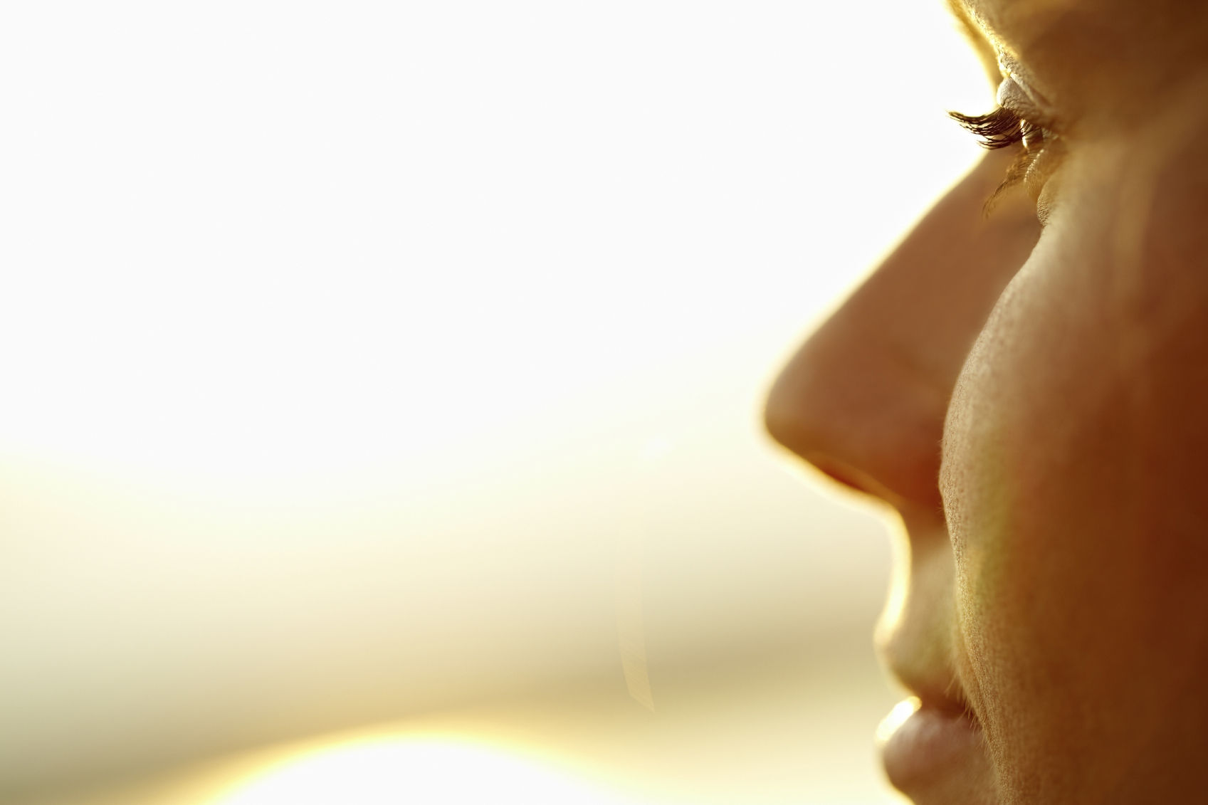 Close-up of profile of young woman looking at sun