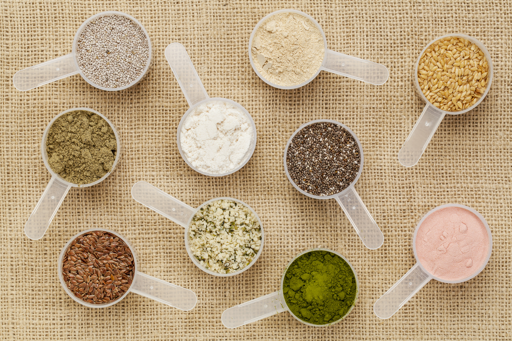 scoops of superfood - healthy seeds and powders (white and black chia, flax, hemp, pomegranate fruit powder, wheatgrass, hemp and whey protein, maca root) on canvas