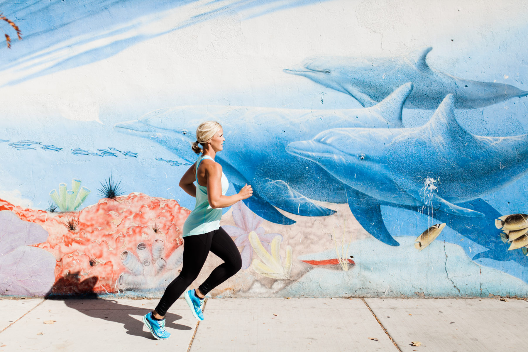 Woman running near a cool mural