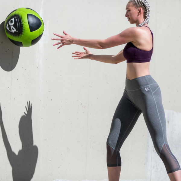 woman pumping out a glutamine fueled ball workout