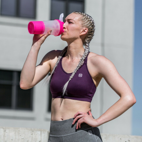 woman drinking l glutamine from a bottle