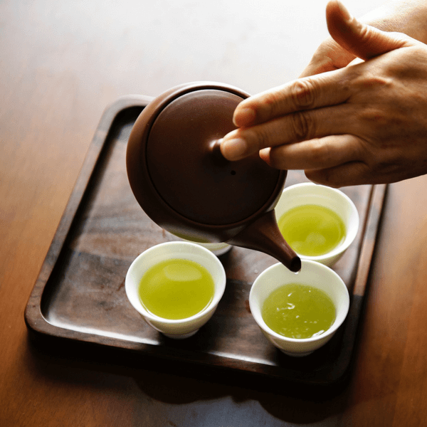 A womans hand pouring several cups of delicious green tea