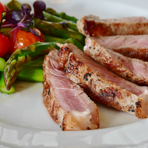 A plate of sliced meat, asparagus, and cherry tomatoes
