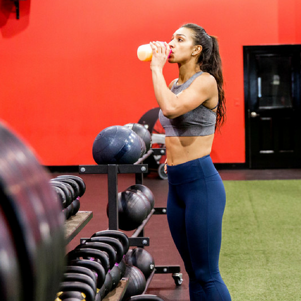 A woman sipping a protein shake while in a gym