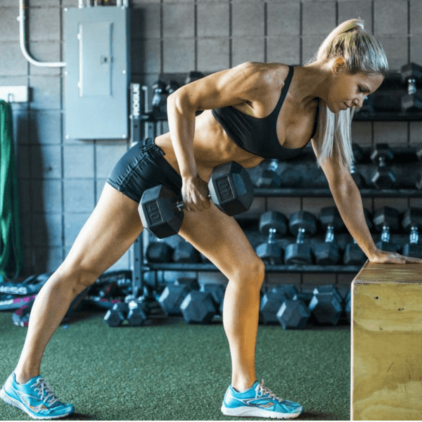 A woman doing single arm dumbbell rows in a gym