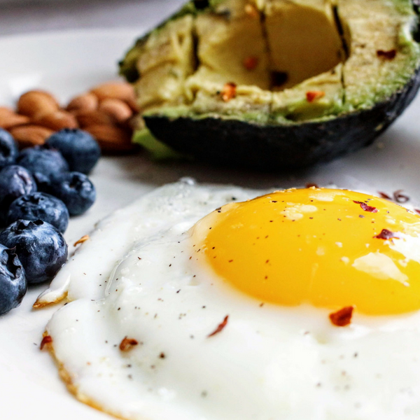 A plate filled with a fried egg, a sliced avocado, almonds, and blueberries. It looks delicious.