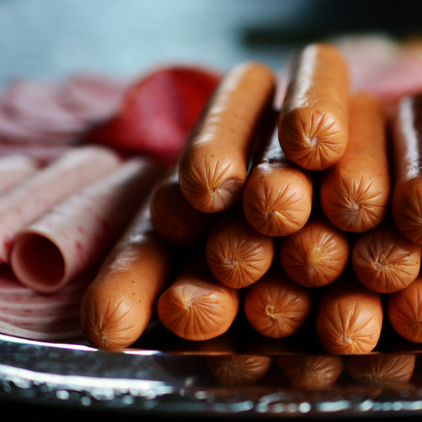 A plate of stacked hot dogs next to some rolled up deli meat slices