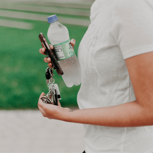 A woman carrying a water bottle, phone, and keys