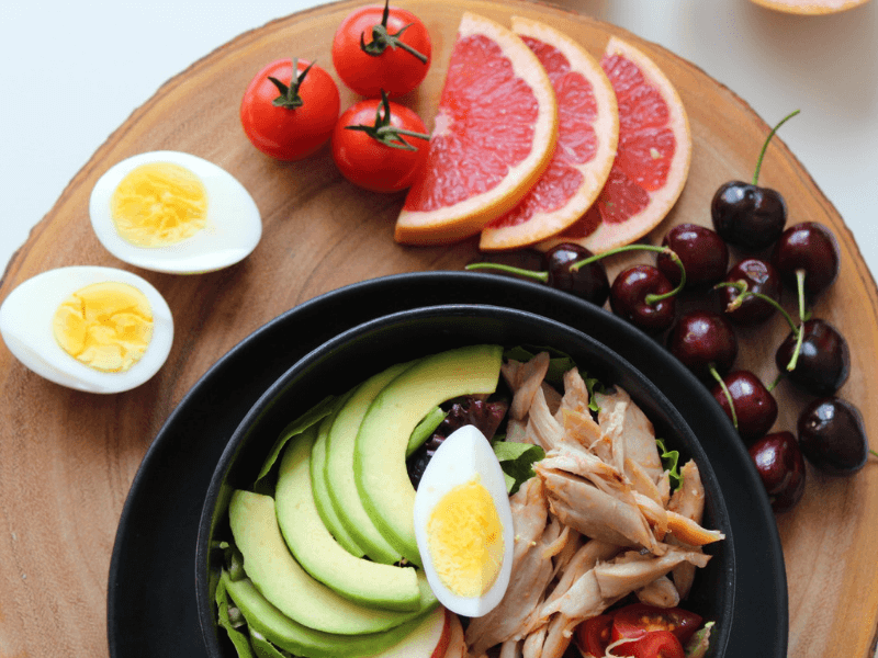 A spread of delicious Mediterranean diet foods including avocado, lean meat, fruits and veggies