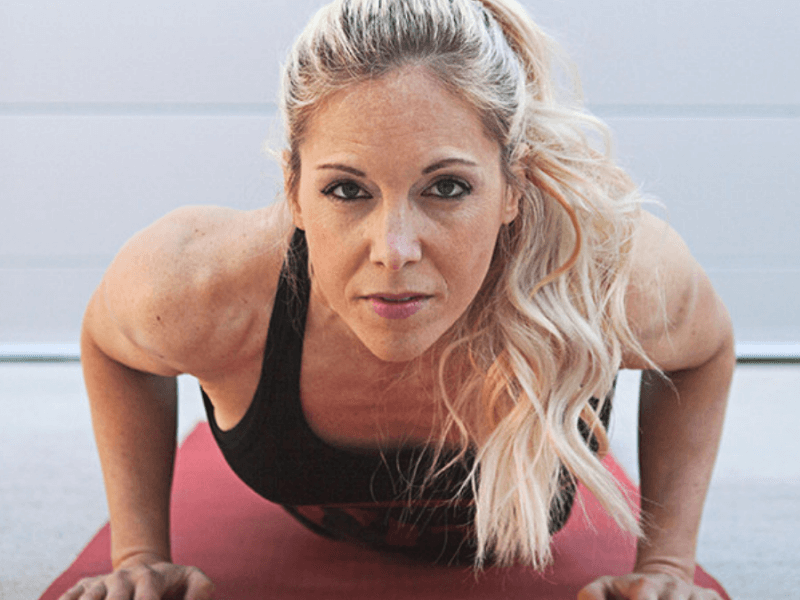 A woman doing a push-up as part of an at home workout routine