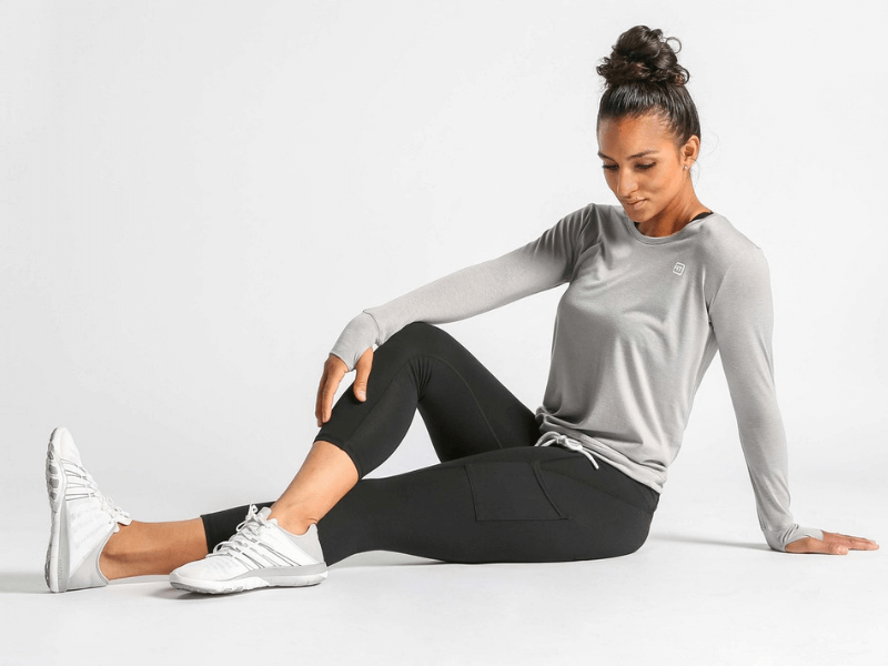 A woman wearing workout clothing and stretching
