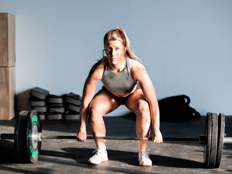 A woman lifting weight without a weight lifting belt