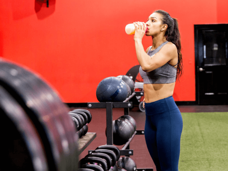 A woman drinking a sucralose sweetened weight loss drink