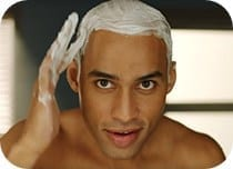 Man applying shaving gel to head
