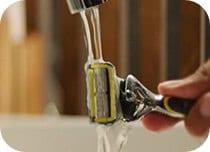Rinsing Gillette Proshield razor under tap