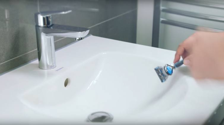 Tapping Gillette razor against sink