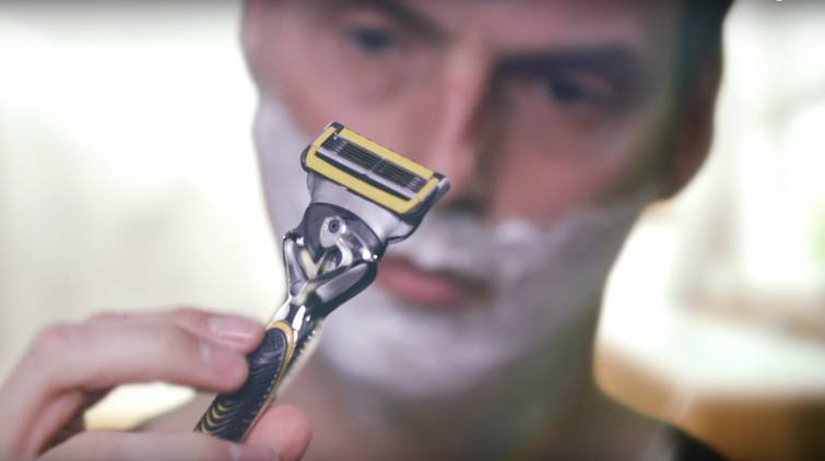 Shaving with five-bladed Gillette razor in yellow and a moisturising layer