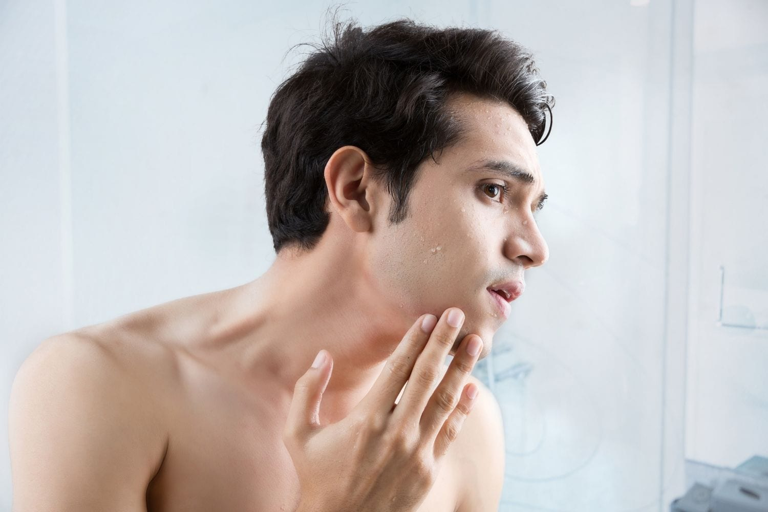 man checking for dry skin after shaving