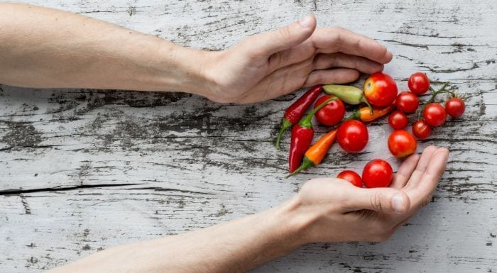 hands holding tomatoes and chillies