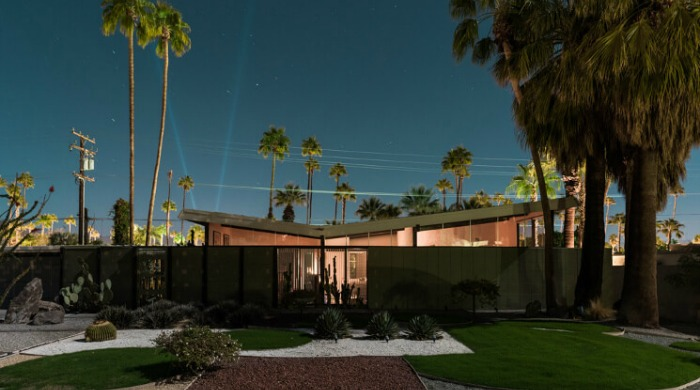 Tom Blachford Midnight Modern: A futuristic home with the lights of Palm Springs behind it in the night sky.