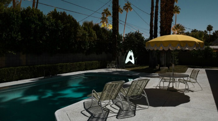 Tom Blachford Midnight Modern: A swimming pool and deck chairs cast in shadow.