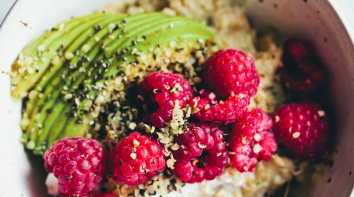 Breakfast Oatmeal Recipes: a bowl of protein boost oatmeal with avocados and raspberries.