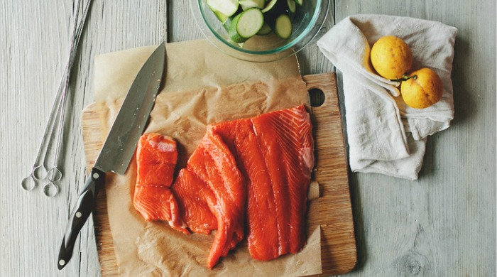 Salmon and other ingredients on a chopping board.