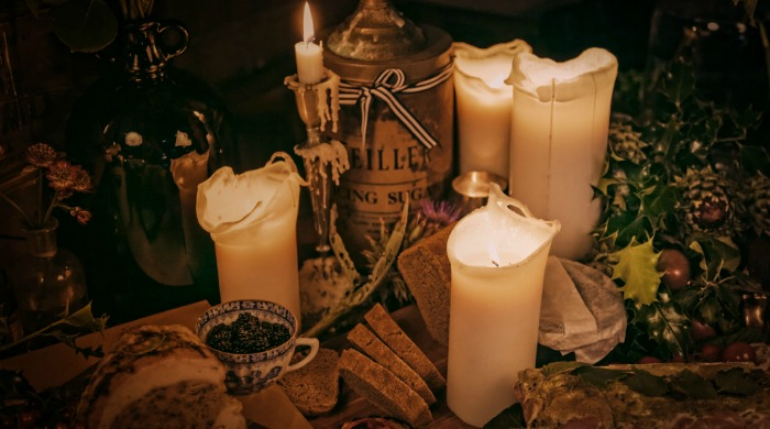 A festive place setting with candles and holly at The Chimney House.