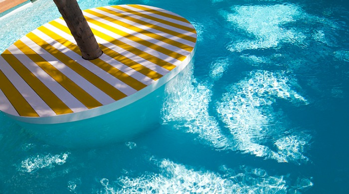 La Banane: A circular, white and yellow striped platform built into a pool with a palm tree growing out of the centre.