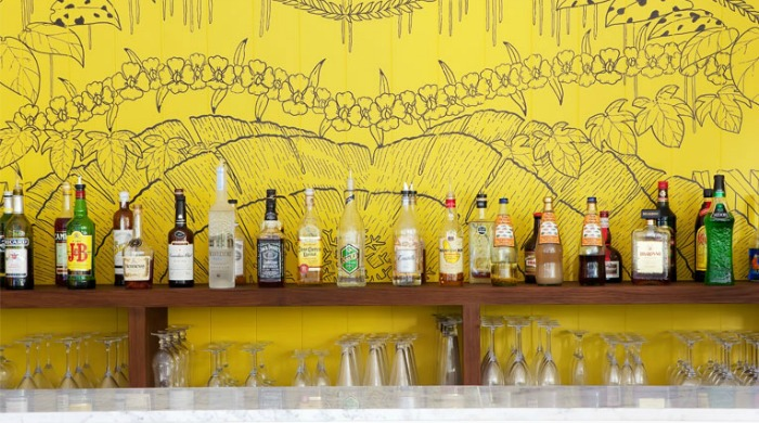 La Banane: A bar filled with a wide range of exotic spirits against a bright yellow, patterned wall.