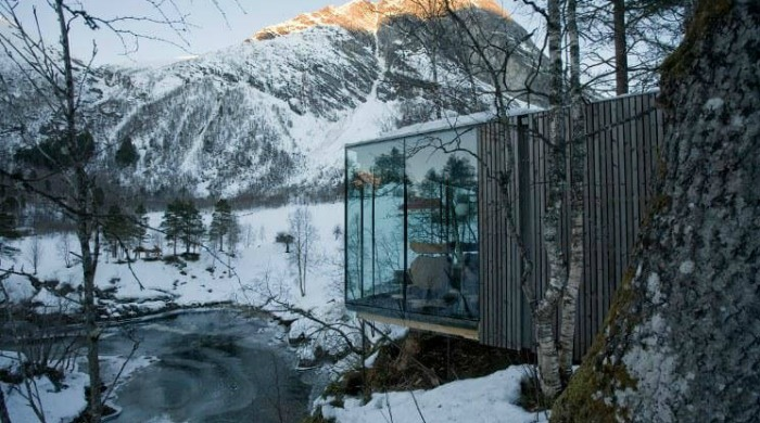 The Juvet Hotel, Norway: A side view of the hotel that seems to be floating amongst the trees, looking out on to a snowy mountain.