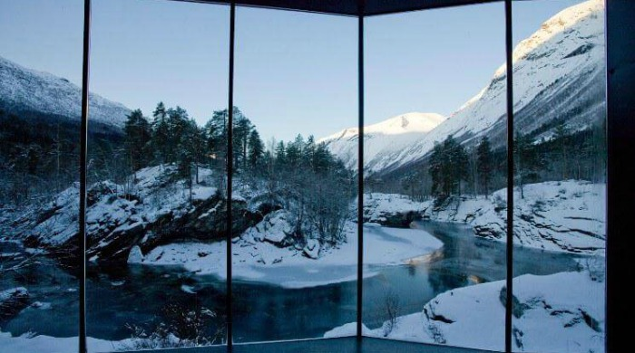 The Juvet Hotel, Norway: A view from inside the hotel looking out on a wintery scene with an island of trees set in a valley amongst snow-capped mountains.