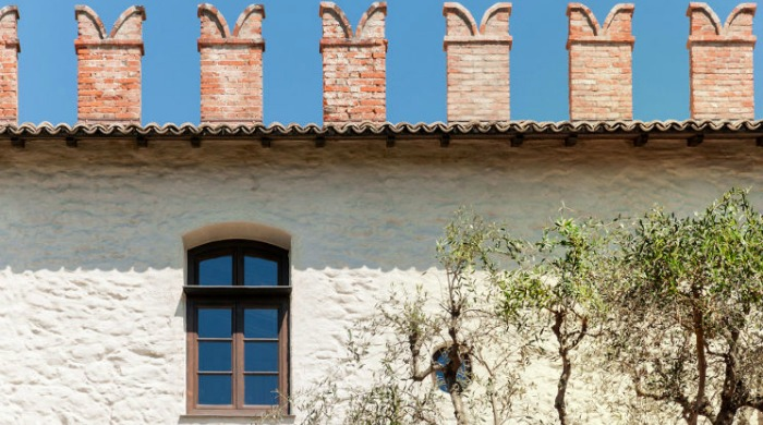 Prati Palai, Lake Garda: The farmhouse roof lined  with brick chimneys against a bright blue sky.
