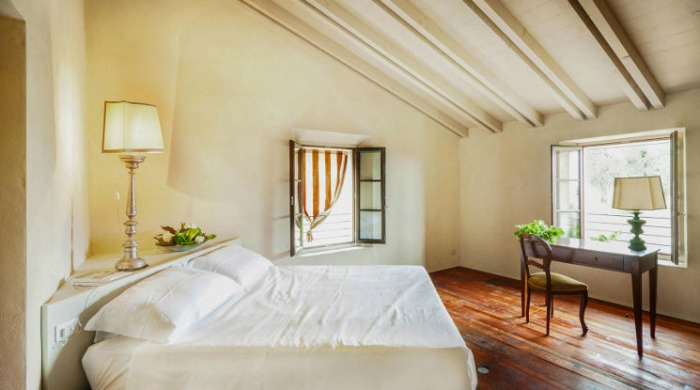 Prati Palai, Lake Garda: A light, airy bedroom with brown wooden floorboards.