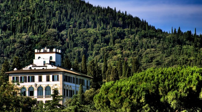 Il Salviatino, Florence: The hotel nestled amongst the trees of the hillside against a blue sky.