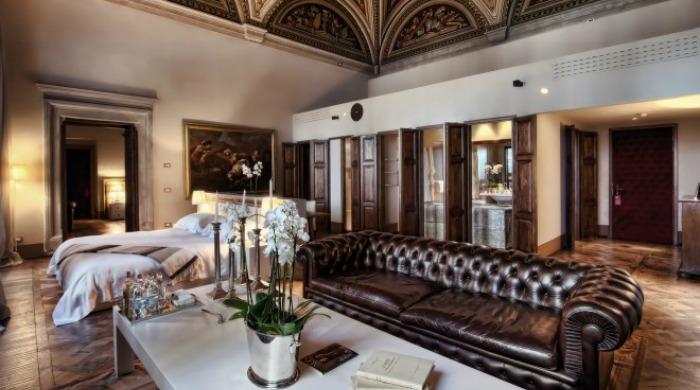 Il Salviatino, Florence: A room with a cream and dark brown colour scheme, including an ornate ceiling, white orchids for decoration and a dark brown leather sofa.