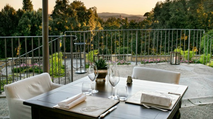 Il Salviatino, Florence: A table for two set on a balcony overlooking the landscape and surrounding trees.